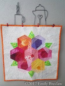 Bright hexagon wallhanging featuring a bouquet of brightly colored flowers and leaves
